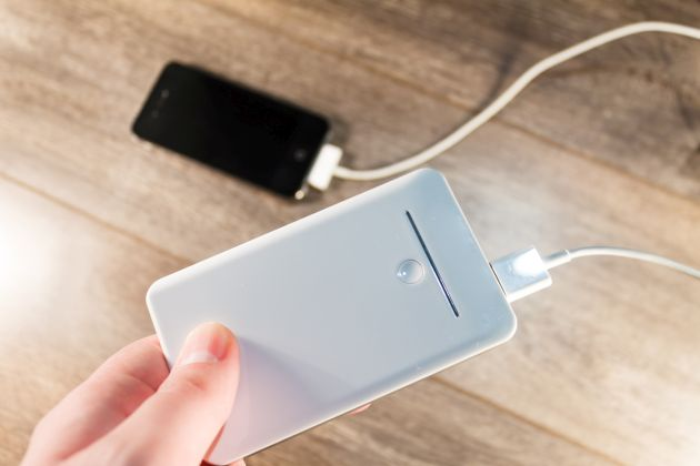 White portable charger is connected to a modern black phone
